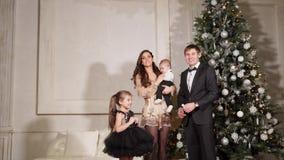 I genitori ed i bambini stanno vicino all'albero che del nuovo anno vogliono celebrare il nuovo anno loro a casa stock footage