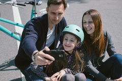 I genitori ed i bambini felici prendono la foto con una bici, pattinano fotografie stock libere da diritti