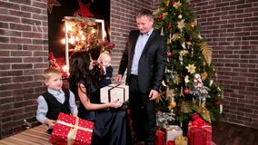 I genitori ed i bambini in vacanza, marito dà i regali alla suoi moglie e bambini, una festa di Natale nella famiglia, il padre archivi video