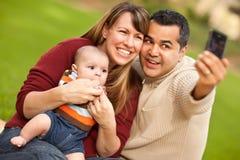 I genitori ed il bambino della corsa Mixed catturano la loro foto Immagine Stock