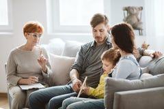 I genitori ed il terapista stanno sedendo sullo strato che parla del loro bambino fotografia stock libera da diritti