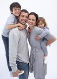 I genitori felici che danno i bambini trasportano sulle spalle i giri immagini stock