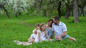 I genitori felici con le figlie parlano e ridono sul plaid nel parco di stagione primaverile video d archivio