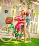 I genitori felici con un bambino, figlia, imparano guidare una bici, vacanze estive di stile di vita della famiglia a casa immagini stock