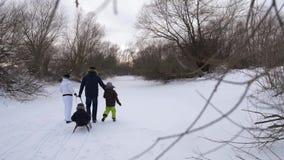 I genitori felici vanno la distanza nella trazione di più giovane figlio sledging Nel frattempo, il figlio più anziano dei fermi  video d archivio