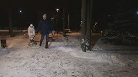 I genitori rotola la figlia sulla slitta nel parco dell'inverno al rallentatore archivi video