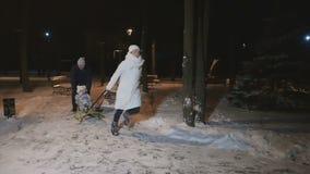 I genitori rotola la figlia sulla slitta nel parco dell'inverno al rallentatore stock footage