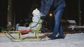 I genitori rotola la loro piccola figlia sulla slitta nel parco dell'inverno di sera archivi video