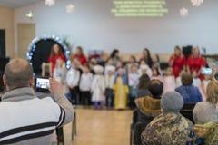 i genitori stanno guardando i bambini della prestazione nell'asilo Una festa dei bambini nell'asilo blurry fotografia stock