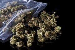 I germogli medici della cannabis hanno sparso dal pacchetto sul nero dal lato Fotografie Stock