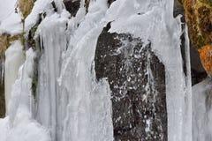 I ghiaccioli del ghiaccio appendono sulle rocce della montagna in un giorno di inverno freddo Immagine Stock