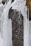 I ghiaccioli del ghiaccio appendono sulle rocce della montagna in un giorno di inverno freddo con wat Fotografia Stock