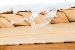 I ghiaccioli meravigliosi si fondono sul tetto di legno con le gocce di acqua La sorgente sta venendo Immagine Stock