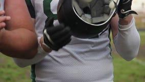 I giocatori di football americano hanno allineato sul giacimento della griglia, applaudente per accogliere favorevolmente il grup video d archivio