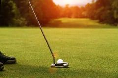 I giocatori di golf stanno mettendo il golf nel campo da golf di sera Immagini Stock Libere da Diritti