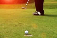 I giocatori di golf stanno mettendo il golf nel campo da golf di sera Fotografia Stock Libera da Diritti