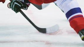 I giocatori di hockey combattono per il disco con i bastoni sul primo piano dell'arena video d archivio