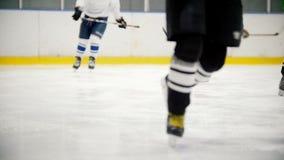 I giocatori di hockey funzionano rapidamente sul ghiaccio durante l'addestramento Vista senza fronti video d archivio