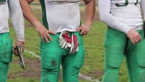 I giocatori di squadra di football americano hanno allineato dopo la partita cruciale per il trofeo tradizionale dell'ascia stock footage