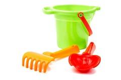 I giocattoli dei bambini bucket la pala ed il rastrello sul bianco Fotografie Stock Libere da Diritti