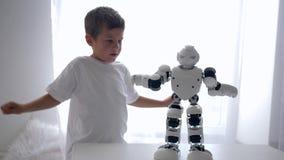 I giocattoli moderni, bambino felice ripete i movimenti del robot astuto con intelligenza artificiale nella stanza luminosa stock footage