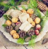 I giocattoli per l'albero di Natale e le pigne in un metallo lanciano, sul nuovo anno di legno anziano del fondo Fotografie Stock