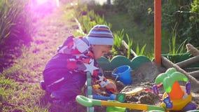 I giochi da bambini con i giocattoli nella sabbiera Giorno pieno di sole di estate Divertimento e giochi all'aperto Immagine Stock
