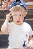 I giochi da bambini con le cuffie, ascoltanti la musica dal vostro telefono Fotografia Stock Libera da Diritti