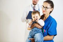 I giochi da bambini sonnolenti con uno stetoscopio sulle mani di un infermiere, nei precedenti è un medico Priorità bassa bianca fotografia stock libera da diritti