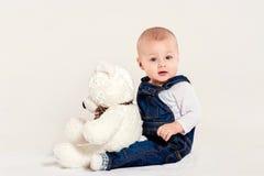 I giochi del ragazzino con un orsacchiotto Fotografia Stock