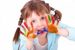 I giochi della bambina con lei hanno colorato le mani Immagini Stock