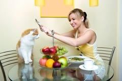 I giochi della ragazza con una cucina del gatto Fotografie Stock