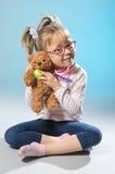 I giochi graziosi della ragazza nel medico tratta un orsacchiotto riguardano le sedere grige Immagini Stock