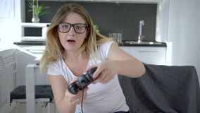 I giochi moderni, ragazza in vetri gioca in video gioco che si siede sulla sedia a casa