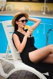 I giovani abbronzano il modello in attrezzatura alla moda dell'estate che gode della festa in piscina, tenente il cocktail sapori immagine stock libera da diritti