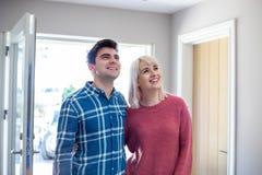 I giovani accoppiano lo sguardo intorno alla casa nuova da affittare insieme o comprare immagini stock libere da diritti