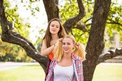 I giovani adolescenti felici dei pantaloni a vita bassa che si divertono di estate parcheggiano Immagini Stock