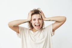 I giovani allegri emozionali hanno tatuato la ragazza che sorride con la bocca aperta che esamina i capelli commoventi della macc Immagine Stock Libera da Diritti