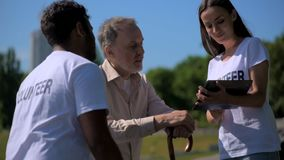 I giovani allegri si offrono volontariamente per mezzo della compressa con un uomo senior video d archivio