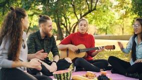 I giovani allegri sono cantanti e muoventi le mani quando la bella ragazza sta giocando la chitarra durante il picnic in parco so stock footage
