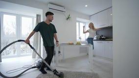I giovani amanti divertenti sta divertendosi in cucina, uomo felice sta ballando con l'aspirapolvere vicino alla giovane donna ch