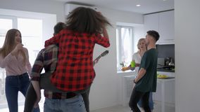 I giovani amici allegri a casa fanno festa divertiresi e ballare mentre la ragazza gioca la chitarra in appartamento archivi video