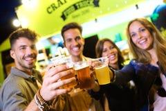 I giovani amici attraenti che esaminano la macchina fotografica mentre tostano con la birra dentro mangiano il mercato della via immagini stock libere da diritti