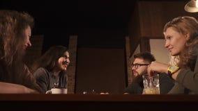 I giovani amici comunicano a vicenda nella barra dopo la conclusione del giorno archivi video