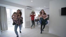I giovani amici divertenti a casa fanno festa avendo corse di a due vie faccia a faccia in appartamento in vacanza al rallentator