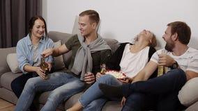 I giovani amici femminili e maschii allegri con le bevande stanno sedendo sul sofà a casa Giovane che prova ad aprire la birra stock footage