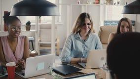 I giovani bei colleghi femminili multietnici felici discutono l'affare dalla tavola dell'ufficio nello spazio coworking 4K del so archivi video