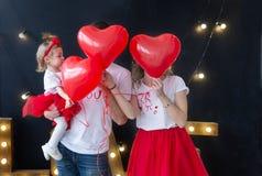 I giovani bei genitori con la neonata che gioca, festa balloons St Giorno del ` s del biglietto di S Fotografie Stock