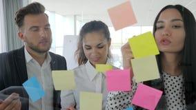 I giovani businessmans che annotano le idee sulle note appiccicose hanno attaccato alla parete di vetro, la gente dell'ufficio ch stock footage