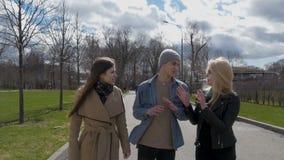 I giovani camminano nel parco, dicono le notizie, comunicano, ridono Buon umore archivi video